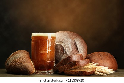 tankard of kvass and rye breads with ears, on wooden table on brown background