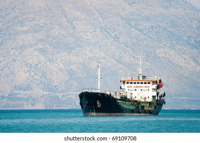 Tanker boat at the Greek sea in front of the mountains