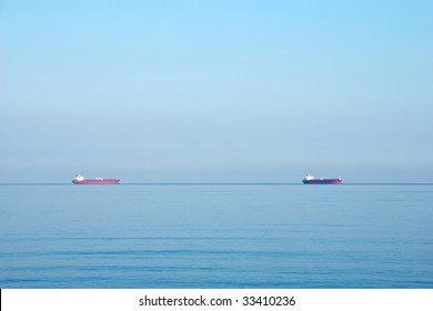 Tanker cargo ships on the horizon under an overcast sky