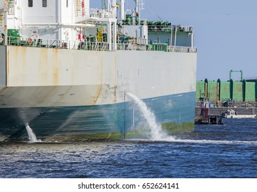 Tanker discharging ballast into the harbor. Water flows from the side. Ship not identifiable. Only part of ship visible.