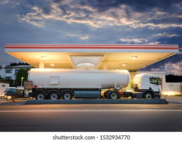 Tanker gas truck delivering fuel at service station against dramatic night sky