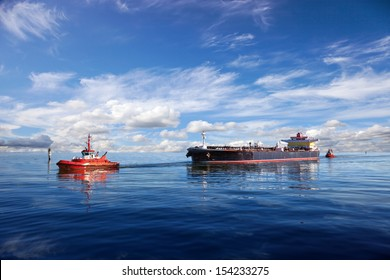 Tanker ship being guided into port by two tugs.