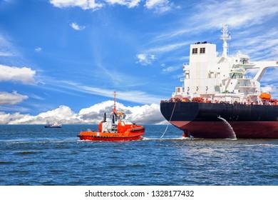 Tanker ship with escorting tug leaving port.