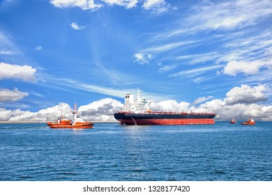 Tanker ship with escorting tugs leaving port.