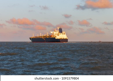 Tanker ship navigating in the Gulf of Mexico with sunset sky in the background and offshore oil platforms in the distance