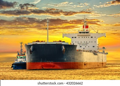 Tanker ship on sea in the rays of the setting sun.