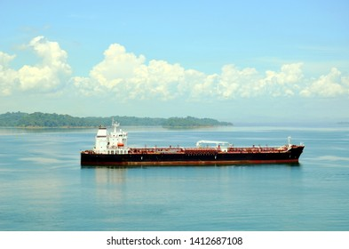 Tanker ship transiting through the Panama Canal on a sunny day.