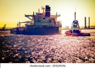 Tanker ship with tugboats on sea. Vintage toned photo.
