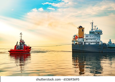 Tanker and tugboat on sea at sunrise.