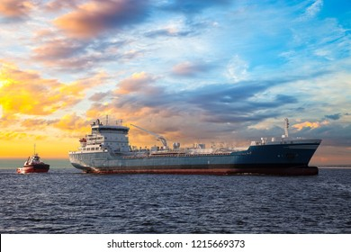 Tanker and tugboat on sea at sunset