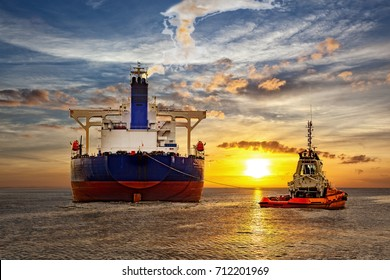 Tankschiff und Schleppboot auf See bei Sonnenuntergang.