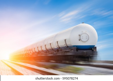 Tanks with gas being transported by rail at sunset