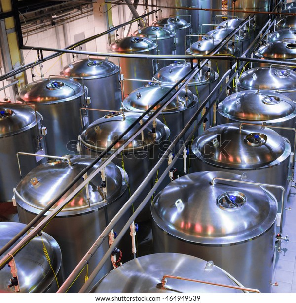 Tanks of stainless steel for the fermentation of beer. beer making shop. Color toning, poor lighting.