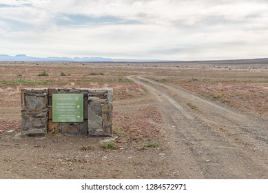 TANKWA KAROO NATIONAL PARK, SOUTH AFRICA, AUGUST 30, 2018: A directional sign and a gravel road in the Tankwa Karoo in the Northern Cape Province of South Africa