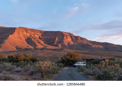 TANKWA KAROO NATIONAL PARK, SOUTH AFRICA, AUGUST 30, 2018: A camping site at Perdekloof in the Tankwa Karoo National Park at sunset. A vehicle is visible