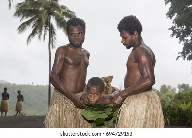 Tanna, Republic of Vanuatu, July 12th, 2014, Men hold a boy on a stretcher with tree leaves, EDITORIAL