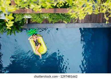 Tanned amazing girl posing in headphones in pool. Overhead portrait of ecstatic lady lying on yellow air mattress during rest at resort.