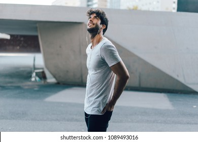 tanned attractive young hipster man dressed in an blank gray t-shirt listening to music through headphones outside.handsome model-style guy enjoys a sunny day listening to internet radio on smartphone
