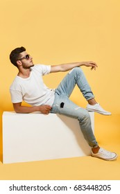Tanned bearded dude sitting on white box dressed in t-shirt and jeans wearing sneakers looking away.
