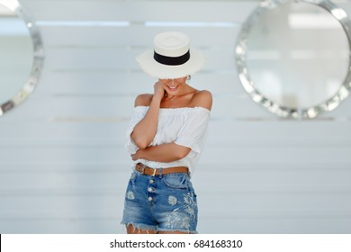Tanned beautiful and sexy girl in a white hat on a white background smiling and looking down in summer