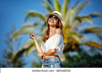 Tanned beautiful and sexy girl in a white hat and glasses smiles, in the summer against a backdrop of palm trees