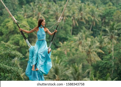 Tanned beautiful woman in a long turquoise dress with a train, riding on a swing. In the background, a rainforest and palm trees. Copy space.