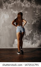 a tanned brunette girl stands posing against the background of a concrete loft wall in short denim shorts and a black tank top and sneakers. athletic with muscles slim with artificial light