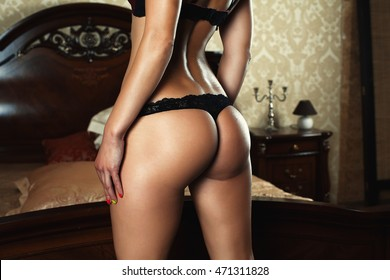 Tanned butt. Beautiful ass. Large buttocks. Girl in black Bode. Sexual shape. beautiful figure. The girl on the bed.
