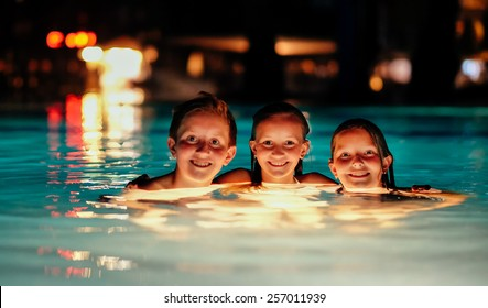 Tanned caucasian kids in a resort swimming pool during night time.
