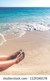 Tanned caucasian woman feet against the turquoise ocean.