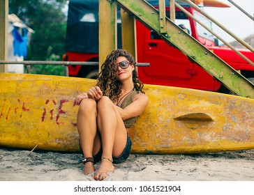 Tanned curly-haired girl resting on the beach near surfboard
