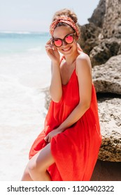Tanned enchanting girl touching her glasses while sitting on rock. Outdoor photo of pretty female model in red attire posing on ocean background.
