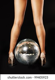 Tanned female legs with disco ball over black background