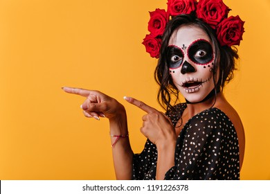 Tanned female model in halloween outfit posing with mouth open. Gorgeous girl in traditional mexican attire celebrating day of the dead.