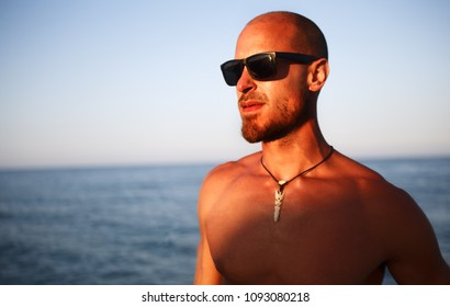 Tanned fit muscular guy shirtless wearing sunglasses with ocean background, bearded fit model outdoors