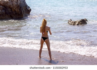 Tanned flexy young lady in bikini takes selfies in the warm waves of Cyprus on sunny beach near the birthplace of Aphrodite