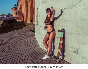 Tanned girl in bathing suit background of wall, taking pictures of herself selfie, online application Internet, making video call. Long hair brunette, skate longboard and bottle water in hand.