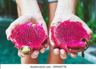tanned girl in a bikini holding a slices of bright juicy tropical dragon fruit. soft focus.