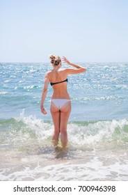 Tanned girl in bikini, on the sea coast of Crimea