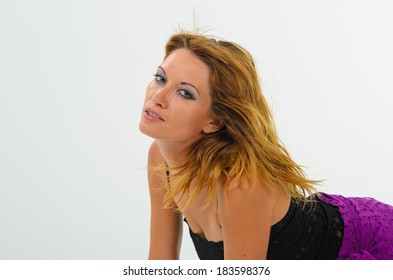Tanned girl in a black tank top and a purple skirt posing in the studio, white background