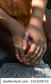 Tanned girl holding her hands on her knee with refracted rainbow prism light creating a pattern on her skin with additional shadows