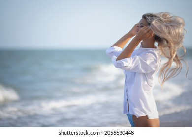 A tanned girl with long blonde hair in a delicate bluish swimsuit and a white light shirt, goes through her long hair on the shore of a stormy sea