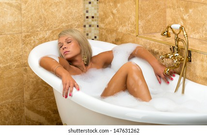 Tanned girl is lying with his eyes closed in the bathroom.