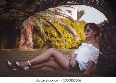 Tanned girl sits on a lawn under a palm tree at tropical resort. Sunburnt young brunette woman in sunglasses sits on a green clearing with her back against a palm tree.