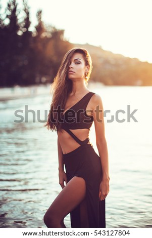 Tanned Girl At Sunset A Beautiful Woman In A Black Dress On The Shore Of