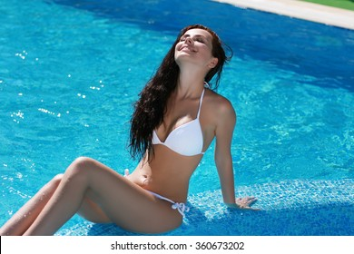 Tanned girl in  white bathing suit in pool