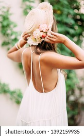 Tanned girl in a white sundress from the back wearing a hat with natural flowers. Summer concept. Fashion blog