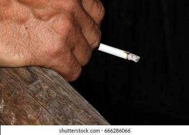 The tanned hand of an elderly Russian villager holding a cigarette in the evening