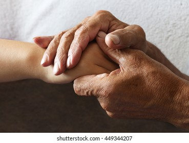 Tanned hands, male hands and bright the hands of a young woman. The elderly man holding the hand of a young woman.