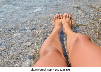 Tanned legs in a cold, fresh sea shallow